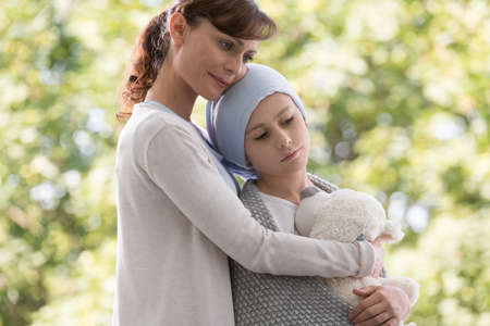 Mother hugging sad daughter with cancer Stock Photo