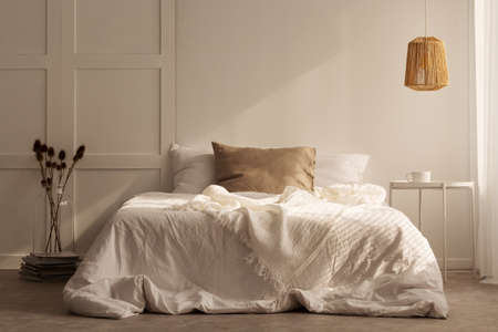 Pillows on white bed between flowers and table in minimal bedroom interior with lamp. Real photo