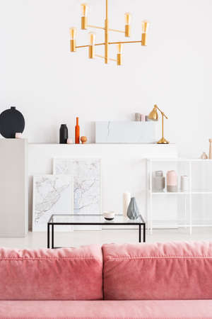 Vertical view of backside of powder pink sofa in white modern living room interior with coffee table, golden chandelier and maps in white frames, real photo