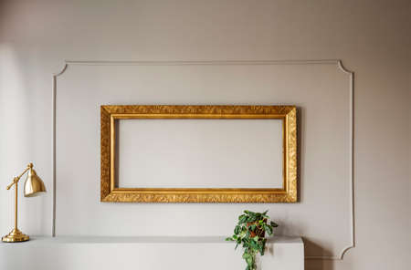 Elegant, empty golden frame inside molding on a gray wall of a stylish living room interior with lamp and a plant. Real photo.