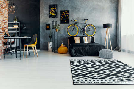Patterned carpet and grey pouf in teenager's bedroom interior with posters and bicycle. Real photo Banque d'images - 110024897