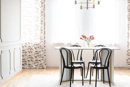 Natural light coming through windows into an elegant dining room interior with black wooden chairs around a marble table