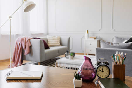 Table with notebook, small plant in pot, glass vase, clock and pencils in cup, real photo with copy space