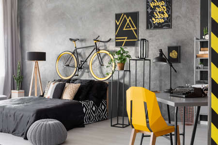 Posters and bike above black bed in grey teenagers room interior with pouf and yellow chair. Real photo
