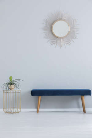 Modern mirror above blue settee and stylish table with plant in golden pot, real photo with copy space