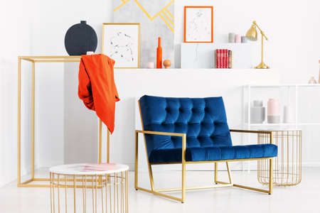 Petrol blue settee in the middle of stylish white living room with golden accessories and lot of art, real photo