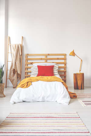 Red pillow and orange blanket on comfortable teenager bed with white bedding in elegant oldschool bedroom interior with copy space on the white wall Stock Photo