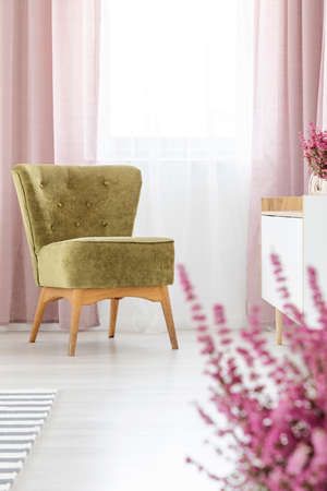 Vertical view of stylish olive green armchair in elegant living room with lilac curtains Фото со стока