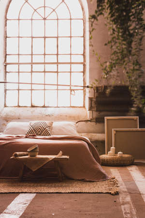 Industrial window in a cozy bedroom interior with a bed, table, frames and radiator. Real photo Stock Photo