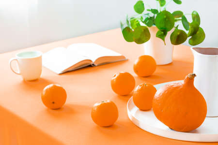 Close-up on table with oranges and pumpkin in dining room interior with plant and book. Real photo Banque d'images - 110007423