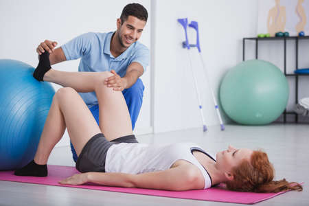 Girl lying on a floor while her physiotherapist is treating her leg Stock Photo