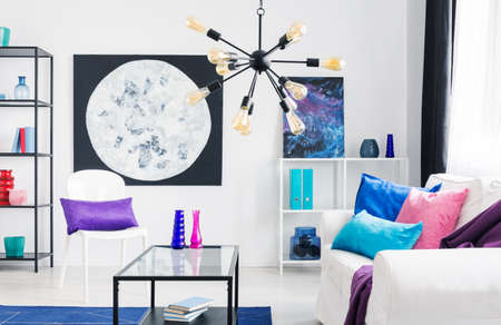 Lamp above table and white couch with pink and blue pillows in loft interior with posters. Real photo