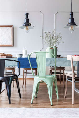 Vintage lamps and green chair at the table in a simple dining room interior. Real photo