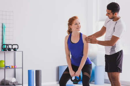 Personal trainer giving instructions to his client who it with is working out with a kettle bell