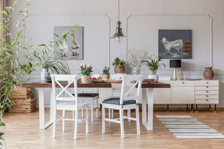 Real photo of a rustical dining room interior with a wooden table, chairs and plants Stock Photo