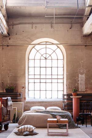 Foto real de una ventana de arco en el interior de un dormitorio wabi sabi con una cama, paredes crudas y una mesa