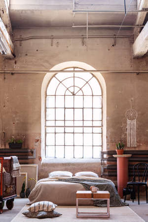 Real photo of an arch window in a wabi sabi bedroom interior with a bed, raw walls and table