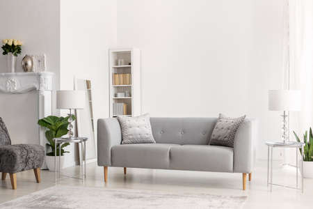 Grey sofa and lamps on silver tables in white apartment interior with flowers and armchair. Real photo