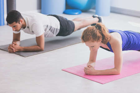 Girl and boy doing plank on a gym