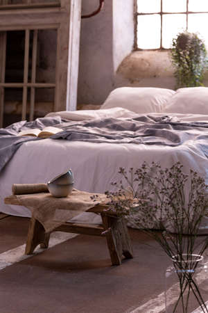 Flower in a vase and small table in front of a bed in a bedroom interior. Real photo Stock Photo