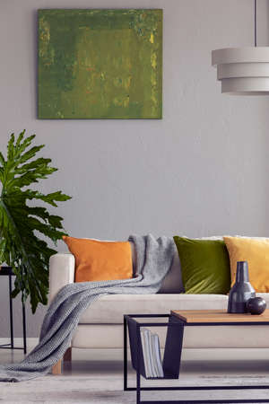 Lamp above wooden table in grey flat interior with green painting and plant next to sofa. Real photo
