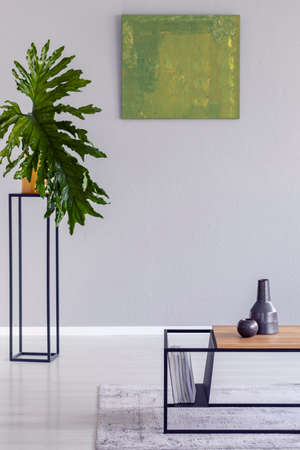 Poster and plant in minimal grey living room interior with wooden table on rug. Real photo