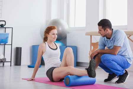 Jeune femme travaillant avec un rouleau en mousse sur un tapis soutenu par son entraîneur