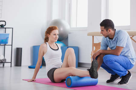 Young woman working out with a foam roller on a mat supported by her trainer Banque d'images - 110007617