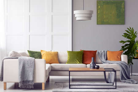 Green cushions and grey blanket on corner sofa in living room interior with lamp above table. Real photo