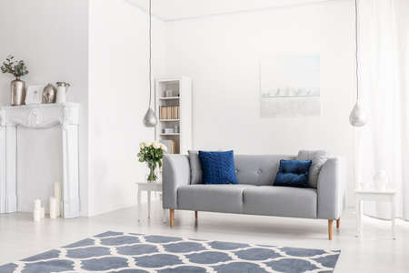 Patterned blue carpet in front of grey sofa in white apartment interior with flowers and lamps. Real photo