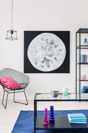 Pink pillow on armchair next to poster in white apartment interior with lamp and table. Real photo