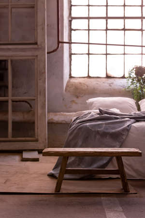 Stool in a bedroom interior with a wooden frame, bed and window in the background. Real photo
