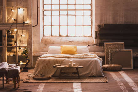 Real photo of a cozy, industrial bedroom interior with a double bed, yellow pillow, window and chain lights