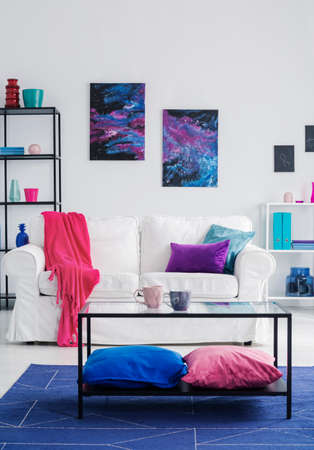 Pillows under table on blue carpet in front of white couch in flat interior with posters. Real photo