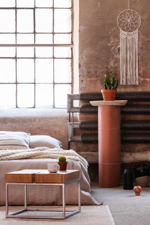 Table in front of a bed, stand with a plant and iron radiator in an industrial bedroom interior. Real photo Banque d'images - 110007705