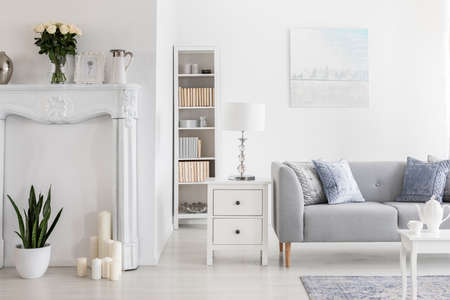 Lamp on cabinet and bookshelf next to grey sofa in white flat interior with painting and flowers. Real photo Stock Photo