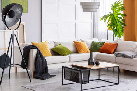 Lamp next to white corner settee with cushions in bright apartment interior with table. Real photo
