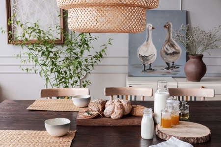 Close-up of fresh bread and milk on a table in a cozy dining room interior on a countryside