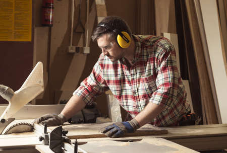 Worker in protective glasses and headphones cutting wood in a sawmill