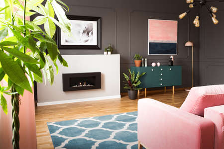 Green plants in a hipster living room interior with molding on dark walls and a pink sofa in front of a burning fireplace. Real photo. Stok Fotoğraf