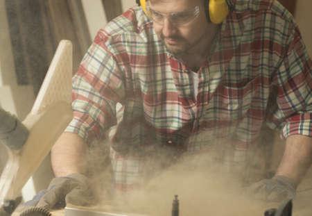 Carpenter working with wood cutting machine
