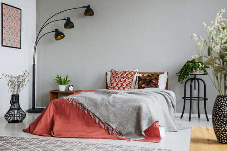 Patterned pillow and grey blanket on king size bed with dark orange duvet in luxury bedroom interior in elegant apartment, real photo with copy space on the wall Reklamní fotografie