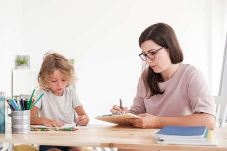 Boy drawing picture while psychologist taking notes during therapy Stock Photo