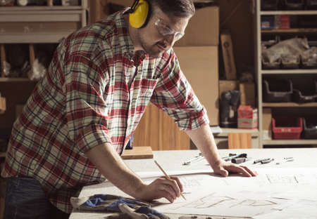 Carpenter drawing a project in a workshop wearing protective headphones