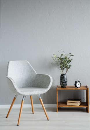Stilvoller grauer Stuhl neben dem Schrank mit Vase und Blumen im modernen Bürointerieur, echtes Foto mit Kopienraum an der leeren Wand