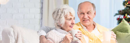 Elder man sitting close his wife on couch