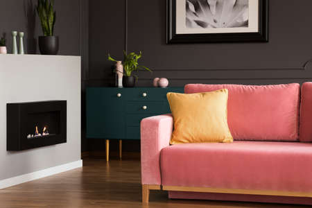 Yellow pillow on a powder pink, velvet sofa and a black, eco burning fireplace in a modern vintage living room interior with dark walls. Real photo.