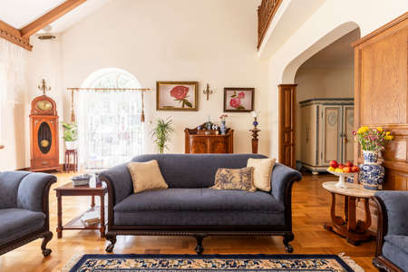 Cobalt blue sofa and other antique furniture on a wooden floor in a spacious living room interior of a classic mansion. Stock Photo