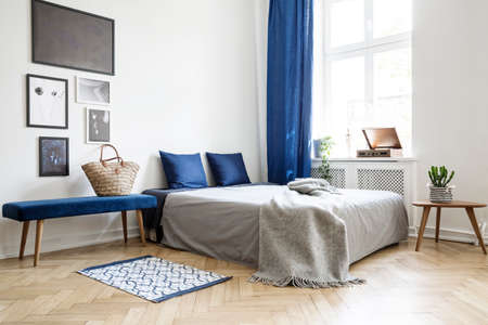 Bedroom design in modern apartment. Bed with dark blue pillows and grey duvet and blanket next to window. Real photo concept