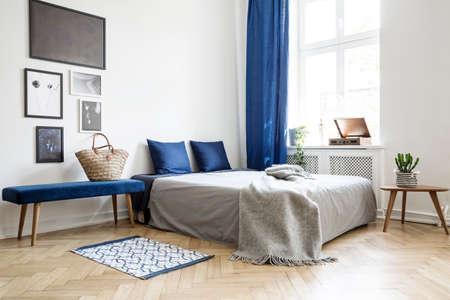 Slaapkamerontwerp in modern appartement. Bed met donkerblauwe kussens en grijs dekbed en deken naast raam. Echt fotoconcept